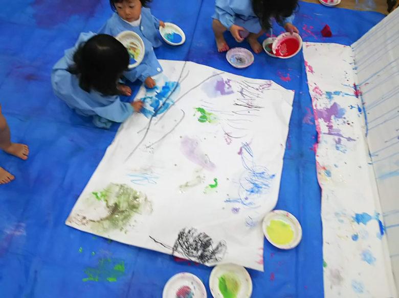 いろんな色の絵の具でペイントする子どもたち