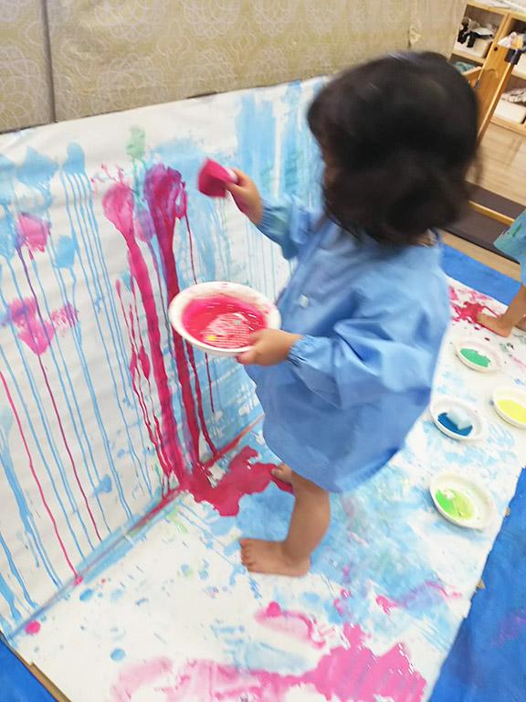 絵の具を染み込ませたスポンジを持ち、紙に立ち向かう子ども