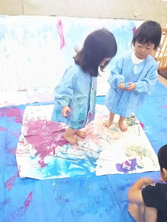 足の裏を使って絵の具でペイントする子ども