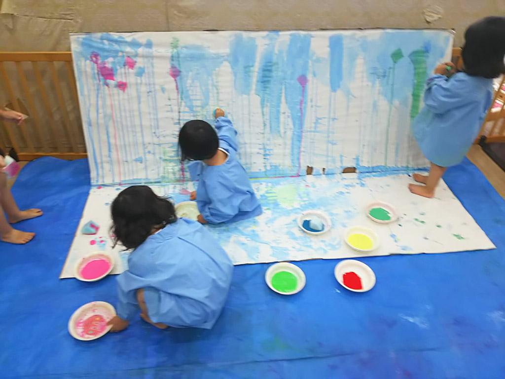 絵の具を染み込ませたスポンジを紙に押し付ける子ども