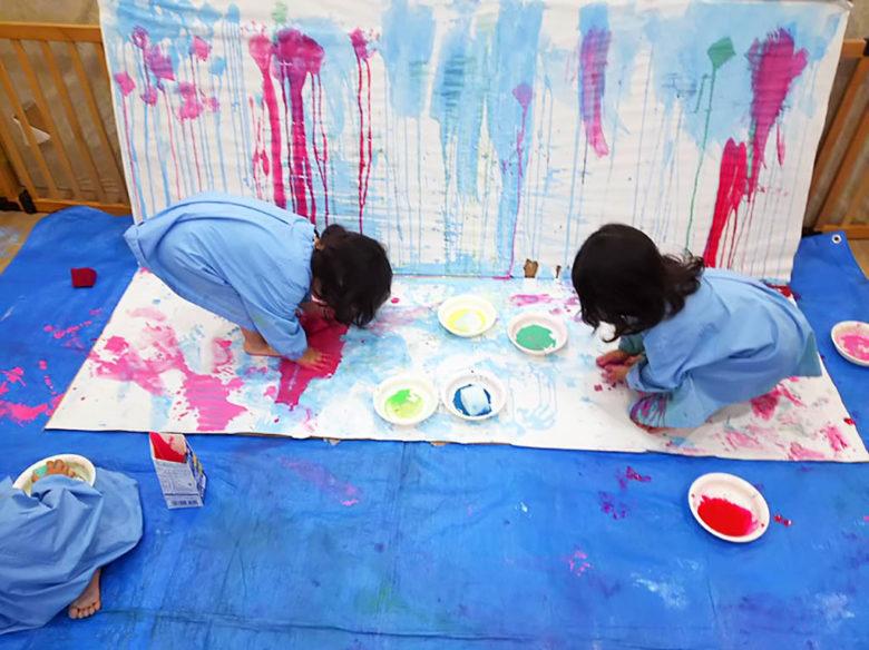 手足を使って絵の具遊びをする子どもたち