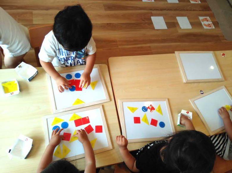マグネット式で形遊びをしている保育園の子供達