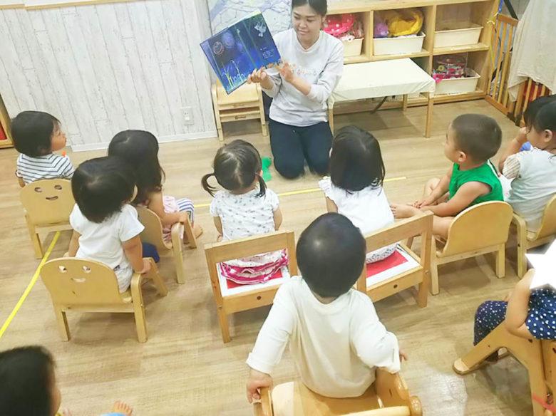 絵本を読んであげる保育士の先生と、熱心に聞いている子供達