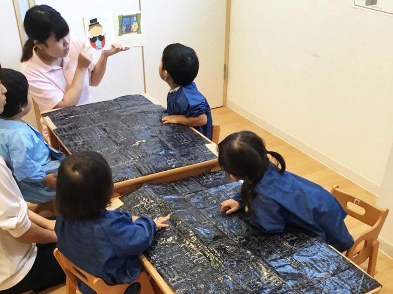 絵本の読み聞かせをする先生と、聞いている子供たち