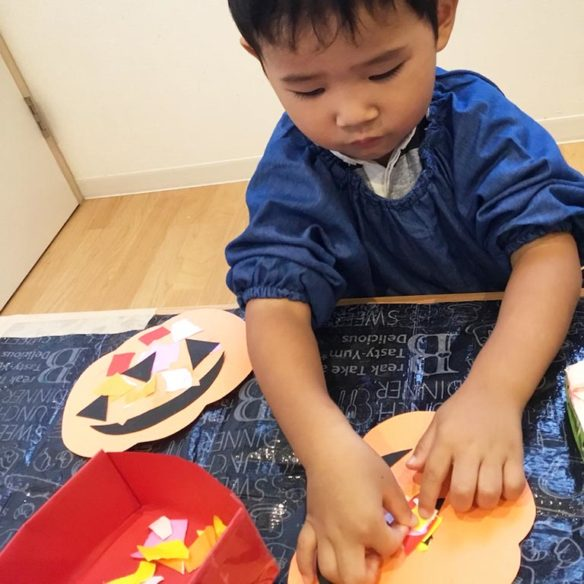 かぼちゃの飾りを作る子ども
