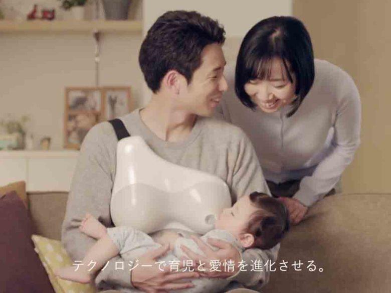 父親がミルクタンクを肩からかけて赤ちゃんにミルクをあげている